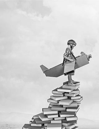 Enfant dans un avion en carton sur une pile de livres
